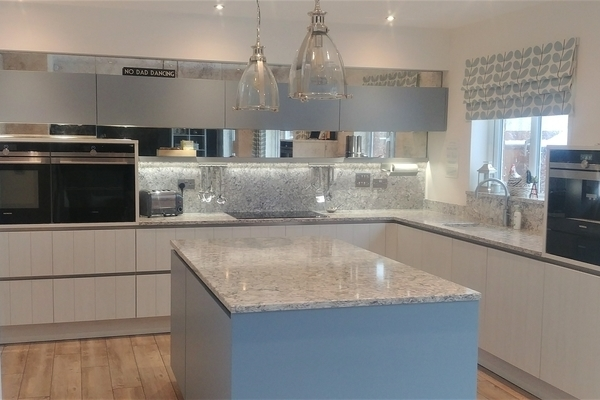 Image of a handleless kitchen design with integrated appliances and a kitchen island with a quartz worktop.
