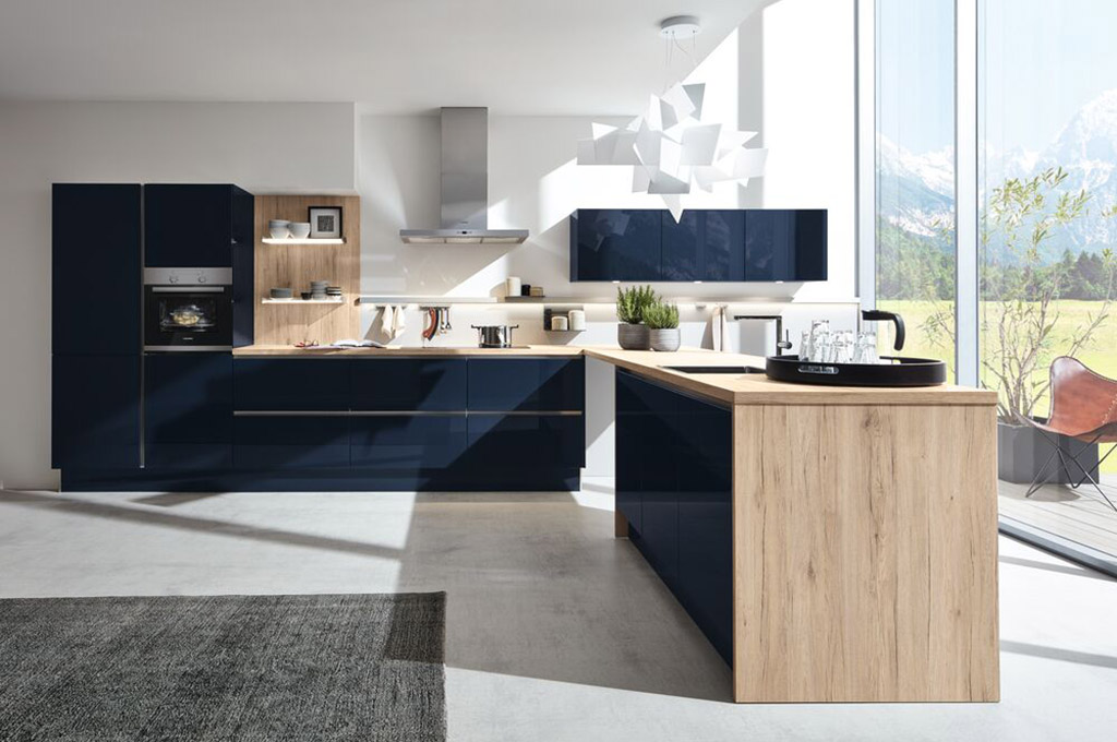 Image of a dark blue and white handleless kitchen design with wooden surfaces and worktops.