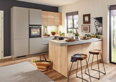 Image of a modern handleless kitchen design featuring matte grey kitchen units and wooden cupboards.