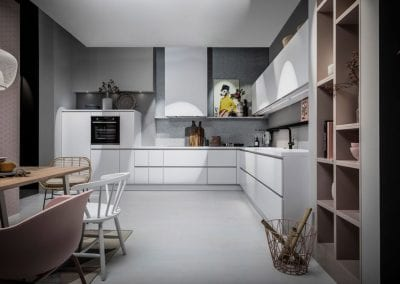 Image of a white and pink handleless kitchen design from Hacker kitchens.