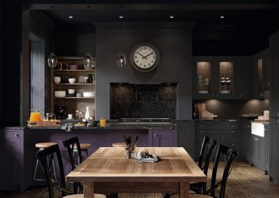 Image of a dark and contemporary kitchen design in an open-plan space.