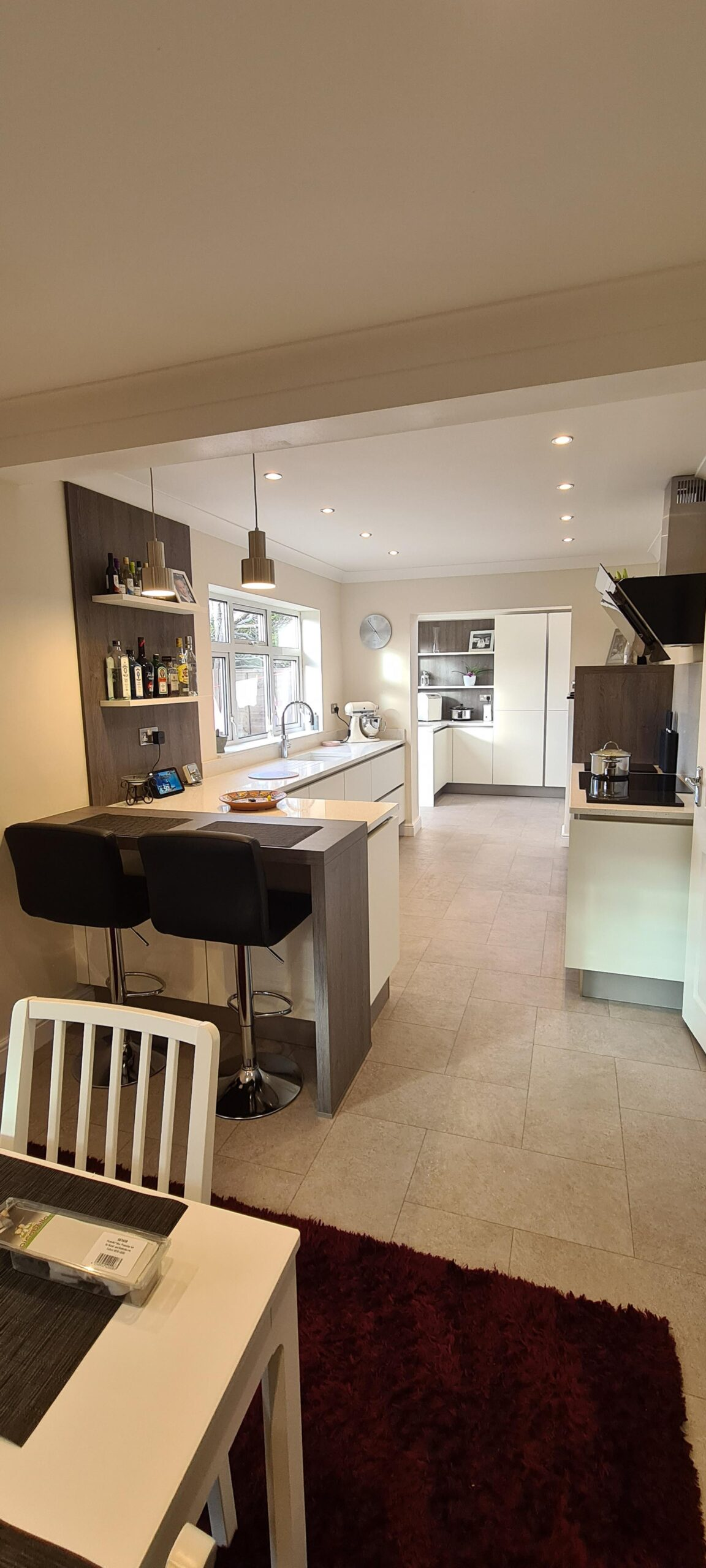 An image of a kitchen with a white marble L shaped counter and a table for eating