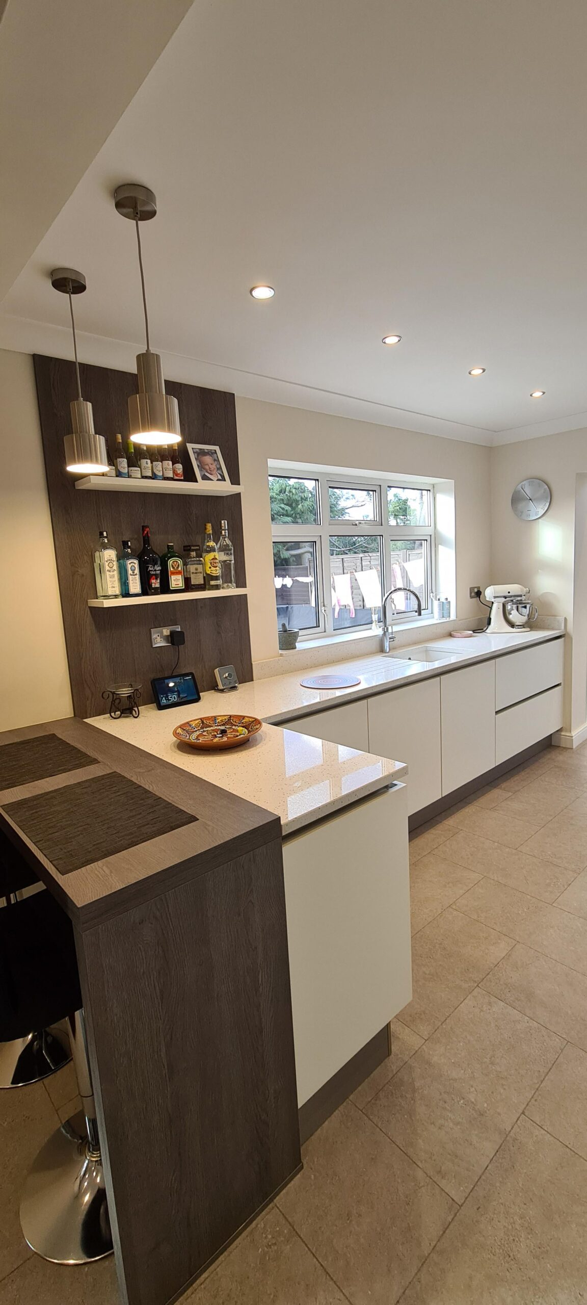 An image of a kitchen with a white marble L shaped counter