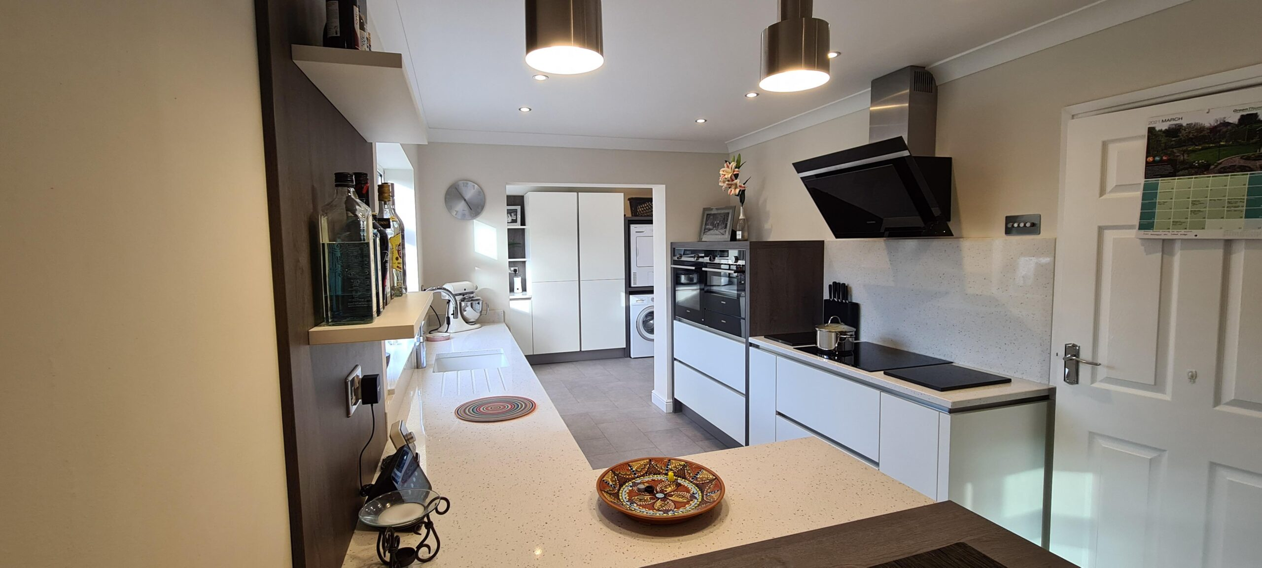 An image of a kitchen with a L shaped white marble counter