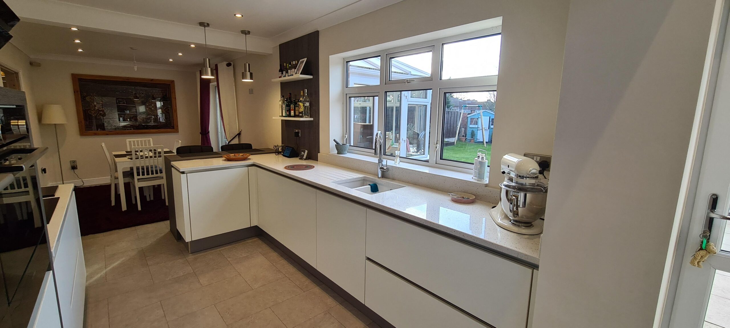 An image of a kitchen with a white marble worktop area