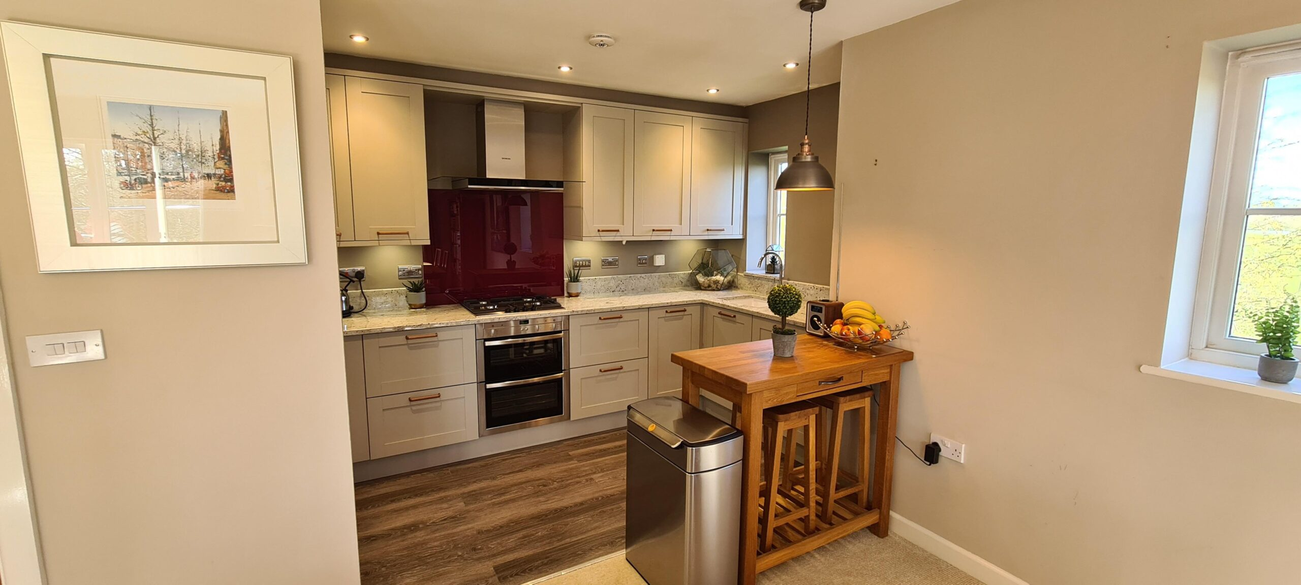 Image of a traditional kitchen design with contemporary elements, such as the integrated kitchen appliance and the white granite worktop.