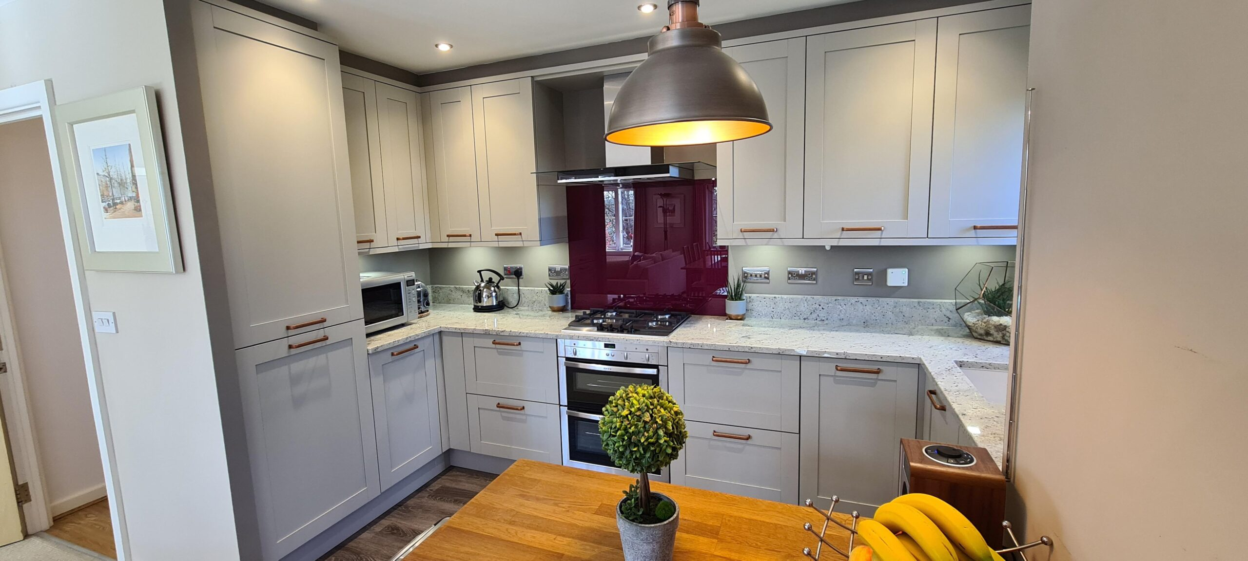 Image of a traditional grey kitchen design with a red splashback and an integrated appliance.