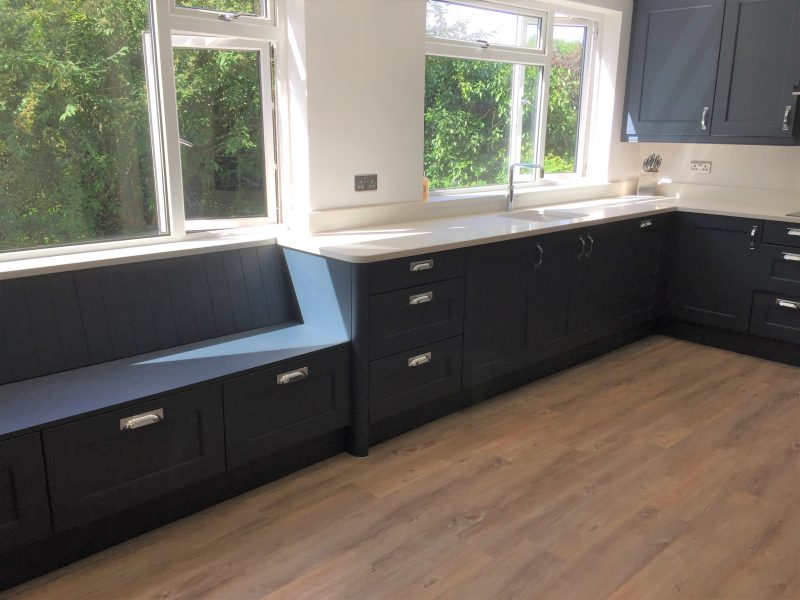 Image of the blue painted wooden kitchen units with quartz worktops.