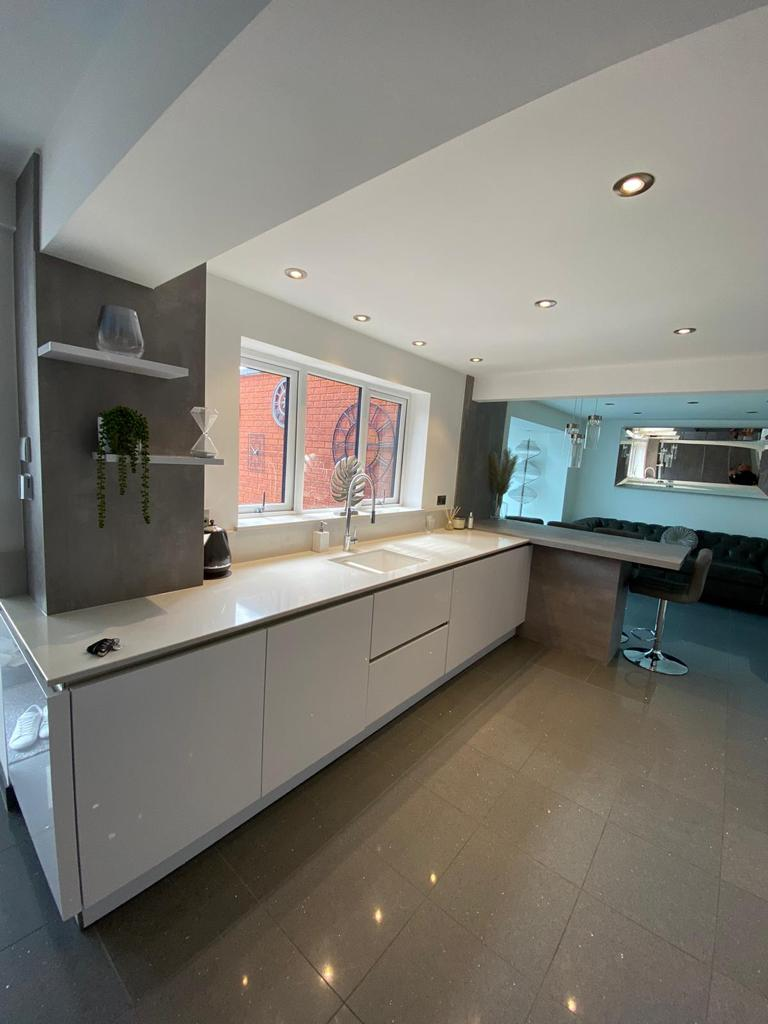 An image of a kitchen with white marble counter tops