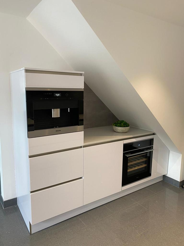 An image of a kitchen with a slanted roof and integrated appliences